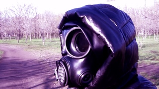 Girl in a black leather down jacket with a hood, in black leather leggings and Czech gas mask Om-90