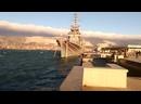 Боевой утёнок плавает возле боевого корабля в шторм