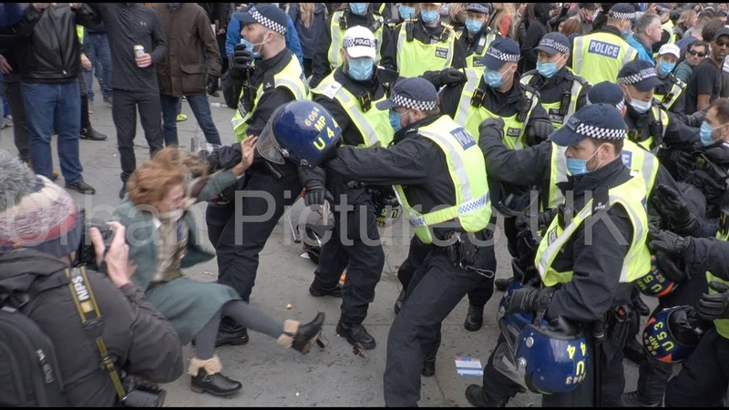 Woman thrown to the ground as police officers scrap with anti-lockdown protesters in London