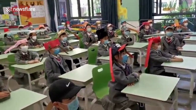 Chinese pupils wear one metre wide hats to keep safe distance with others